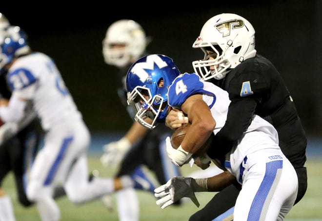 McNary's Devyn Schurr (4) is tackled in the first half of the McNary vs. Lakeridge football game at Lakeridge High School on Friday, Nov. 2, 2018 in Lake Oswego.