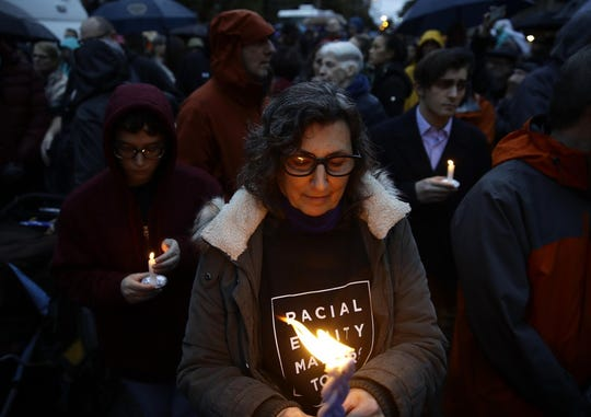 People hold candles as they gather for a vigil in the aftermath of a deadly shooting at the Tree of Life Synagogue in Pittsburgh, Saturday, Oct. 27, 2018.