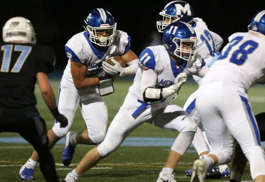 McNary quarterback Erik Barker (12) hands off the ball to Junior Walling (2) on Friday, Nov. 2, 2018.