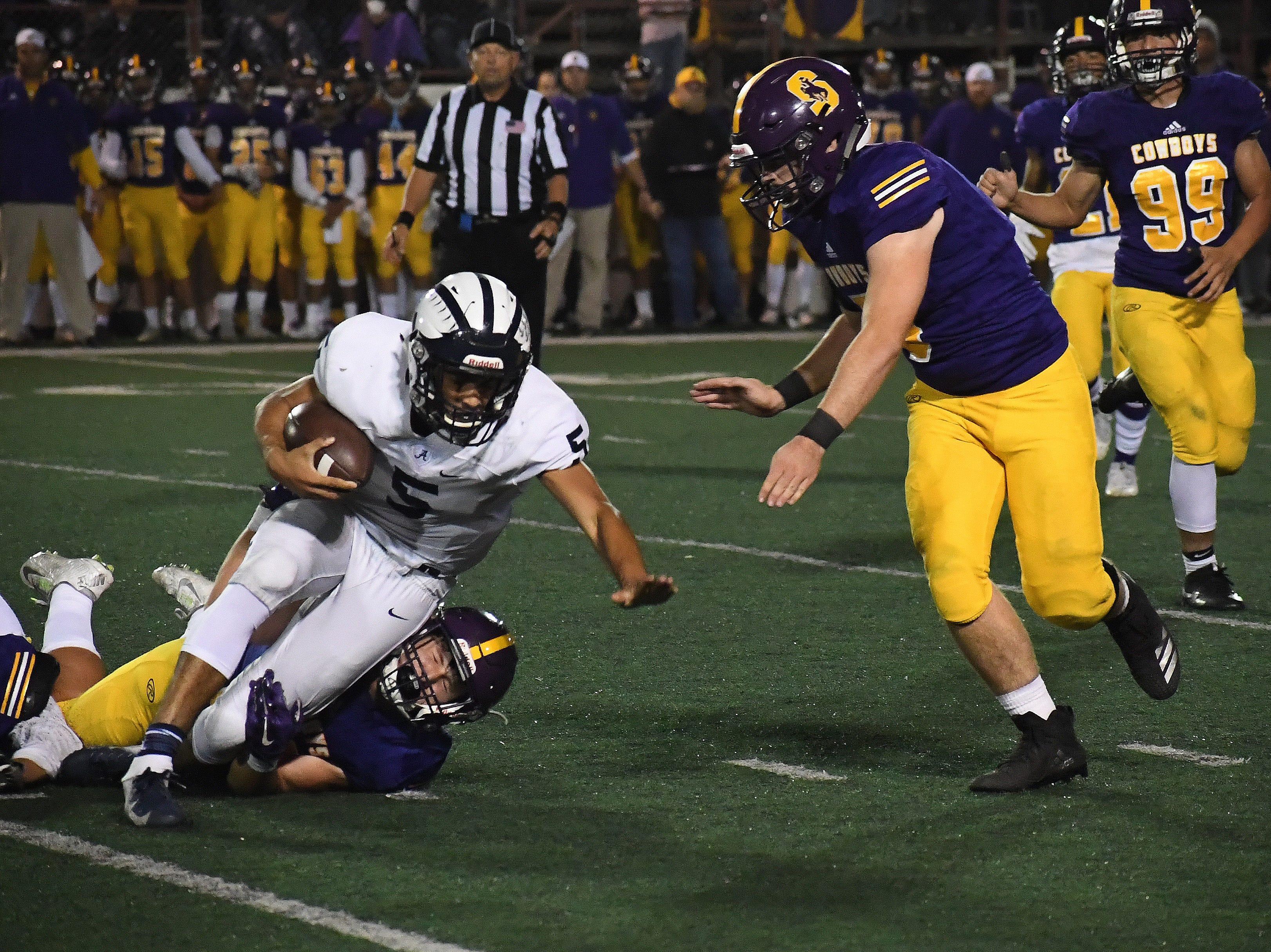 Salinas linebacker Joey Moag (20) wraps up Aptos' quarterback.