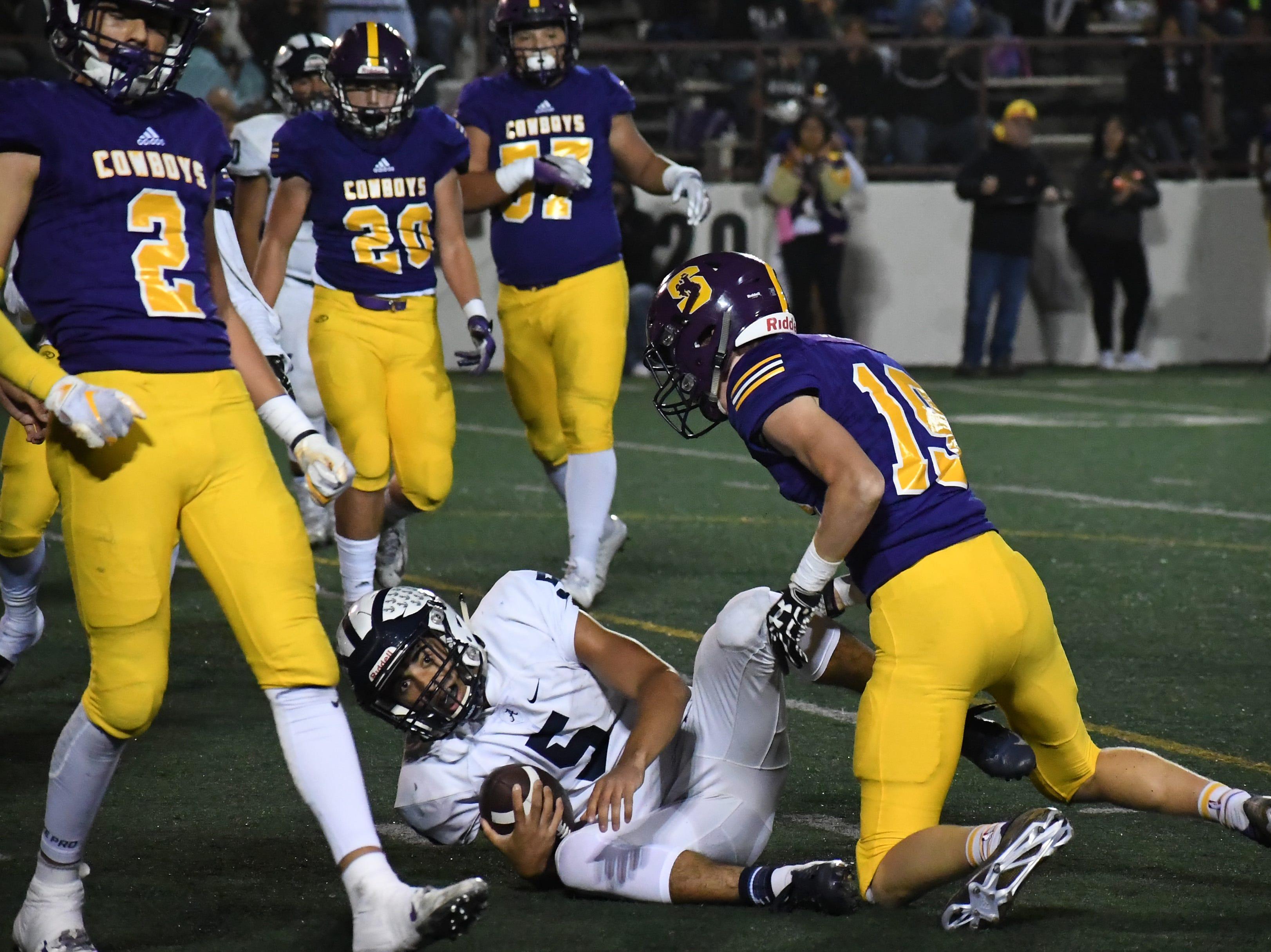 Salinas safety Cade Smith (19) wraps up Aptos' quarterback.