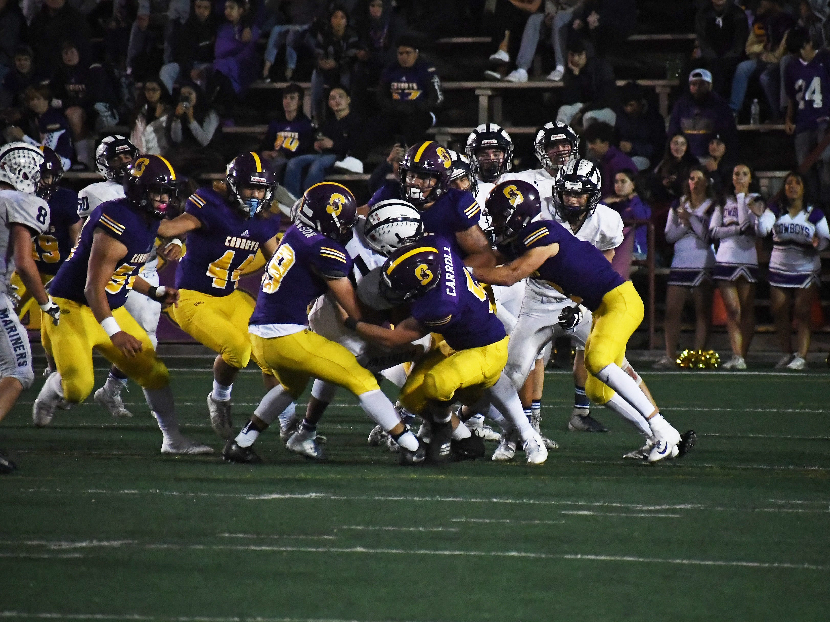 Salinas defenders Tyler Carroll (5), Kyle Lawson (99) and others tackle an Aptos running back behind the line.