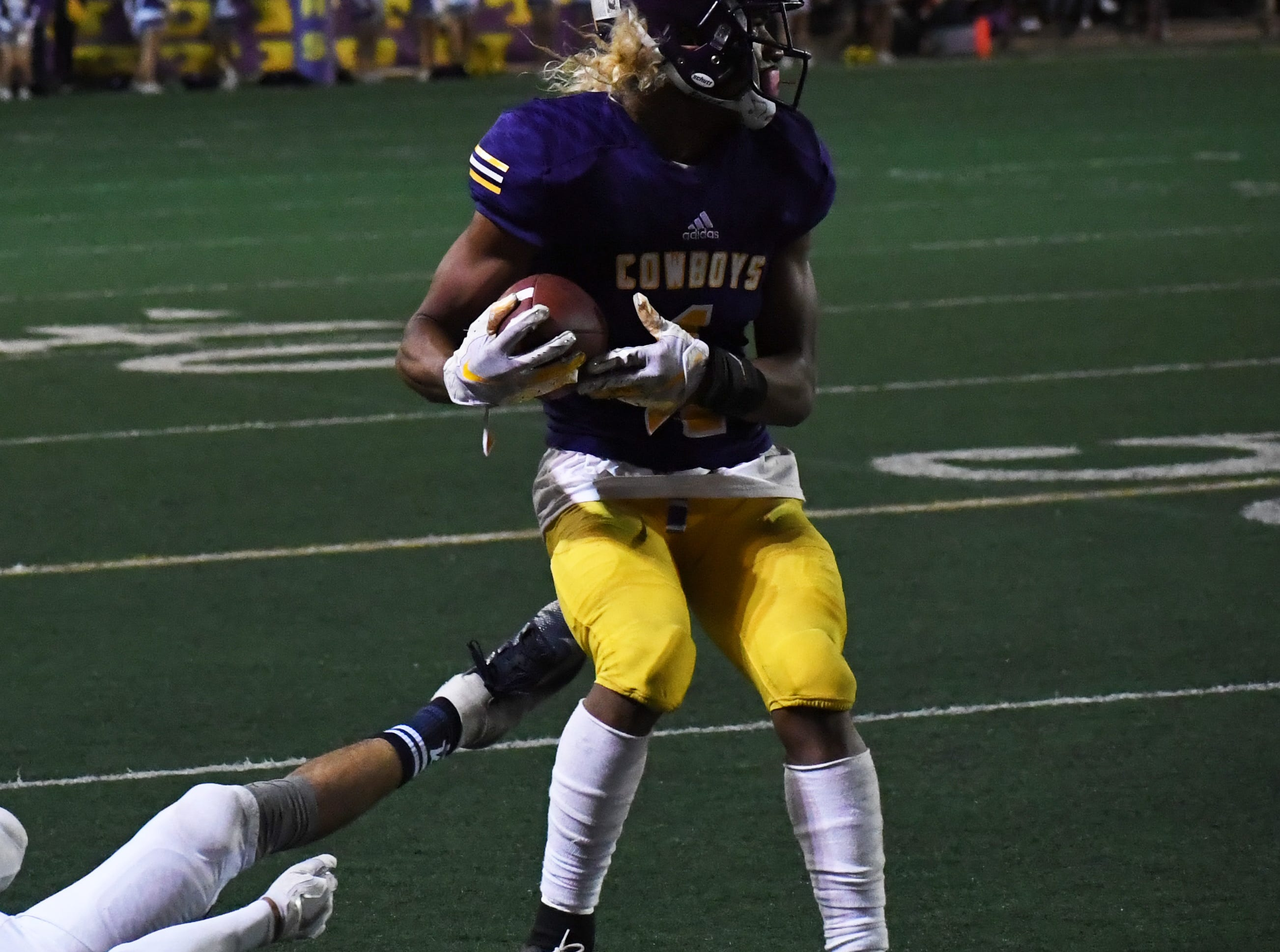 Salinas wide receiver Poe Gaskins Jr. (1) spins out of a tackle and turns upfield.