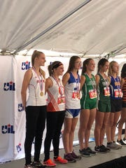 Sonora's Camille Harris, left, accepts her award at the UIL State Cross Country Championships. Harris was fourth in the Class 3A girls race. Wall's Shaylee Shiller, fourth from left, was seventh overall.