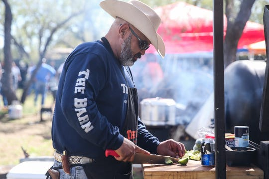 Alex Rivera cuts up lime while he grills during God's County Menudo Cook-off Saturday, Nov. 3, 2018, in north San Angelo.