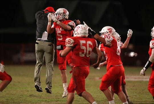 Miles' Mason Bryan (#5) celebrates with his coach and teammates Friday, Nov. 2, 2018 after beating Christoval 21 to 20.