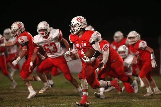 Miles' Davian Martinez (1) rushes past Christoval's defense Friday, Nov. 2, 2018, during the Bulldogs' game in Miles.