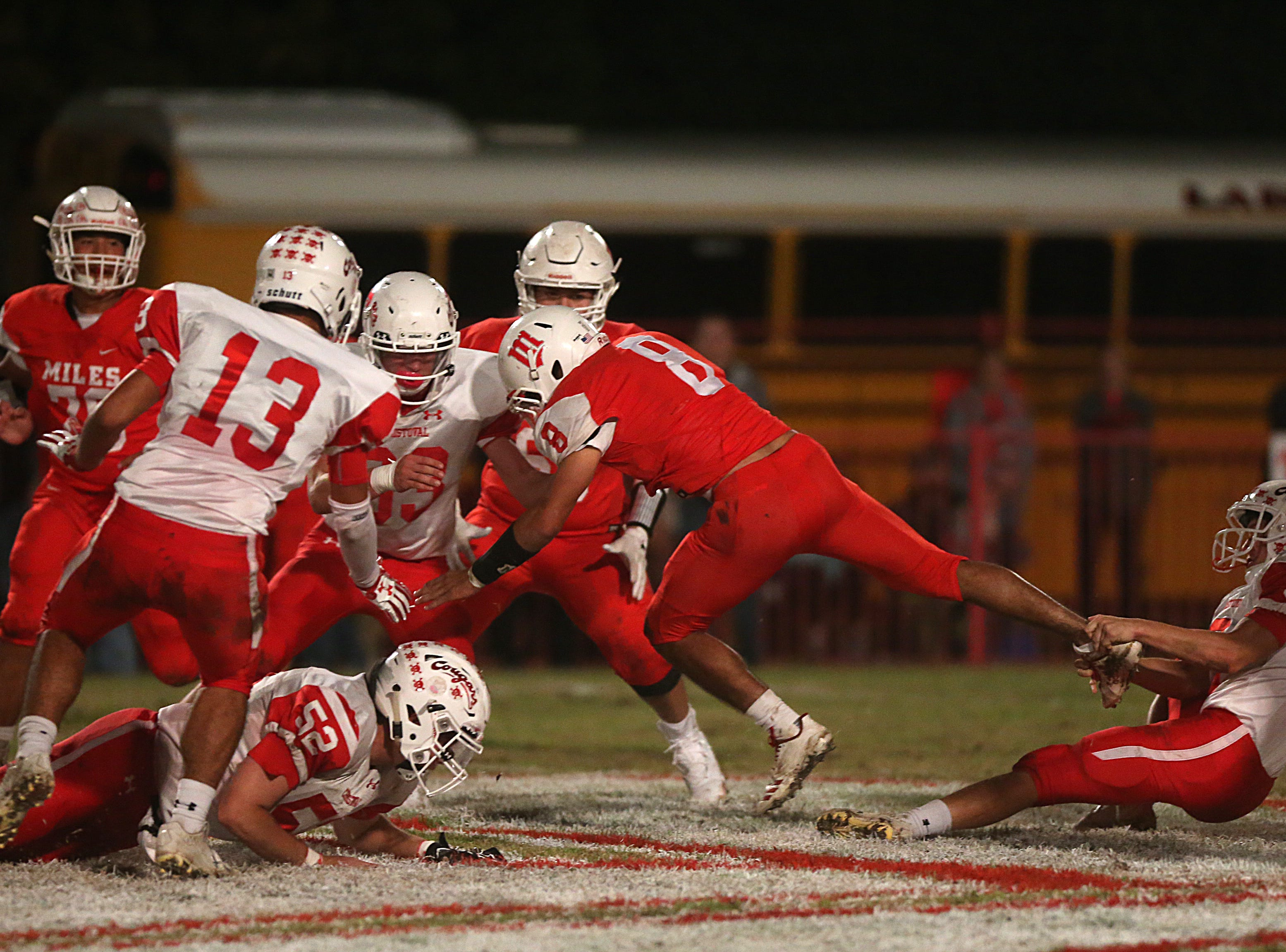 Miles' Jared Flores (#8) gets pulled down by Christoval's Luke Jolly (#9) Friday, Nov. 2, 2018 during their game in Miles.