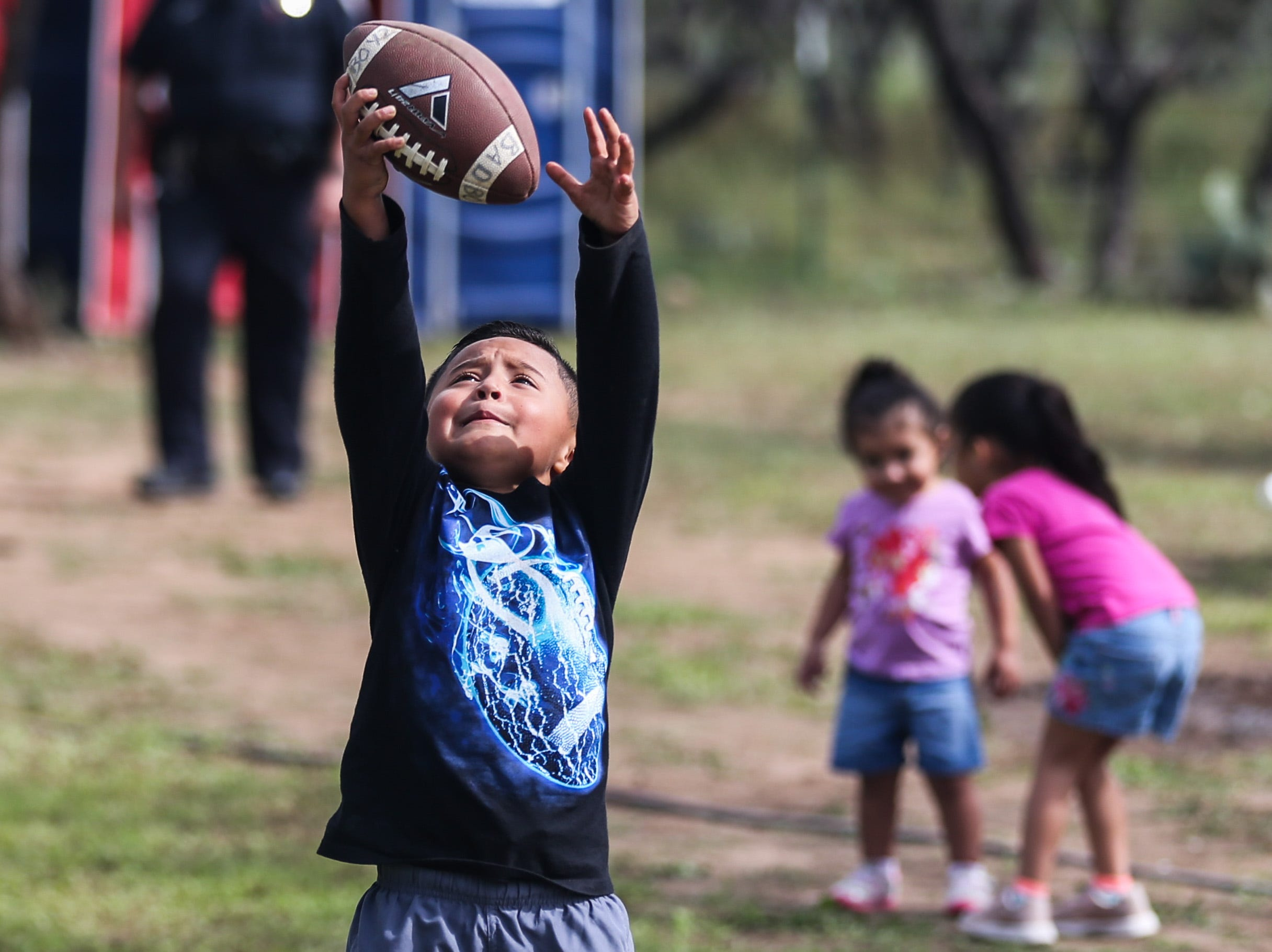 Drake Villarreal, 5, catches a football during God's County Menudo Cook-off Saturday, Nov. 3, 2018, in north San Angelo.