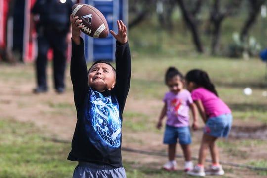 Drake Villarreal, 5, catches a football during God's County Menudo Cook-off Saturday, Nov. 3, 2018, in north San Angelo.