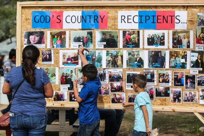 Attendees look over a board featuring past recipients of God's County Menudo Cook-off Saturday, Nov. 3, 2018, in north San Angelo.