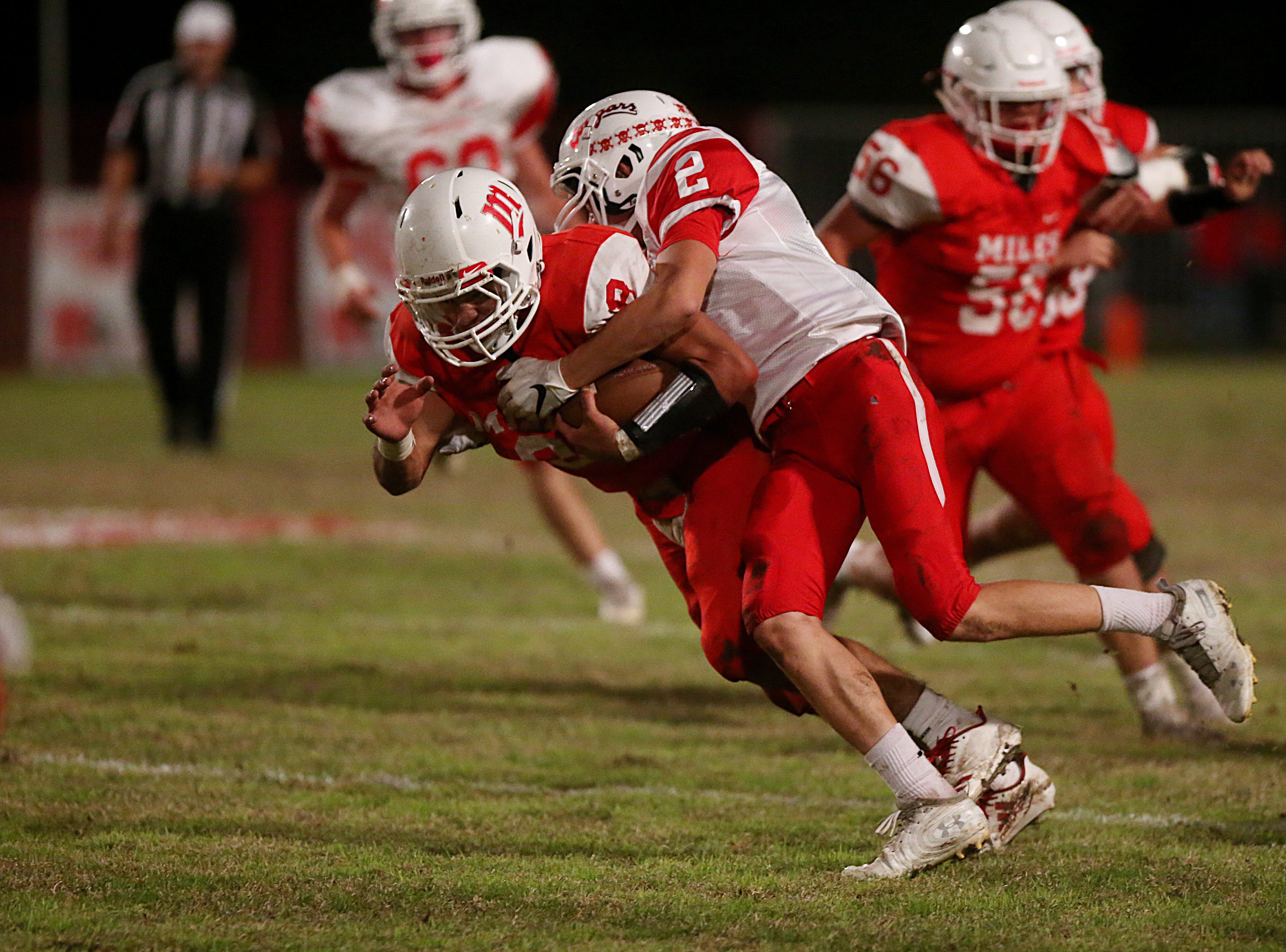 Miles' Jared Flores (#8) is tackled by Christoval's Beau Jolly (#2) Friday, Nov. 2, 2018 during their game in Miles.