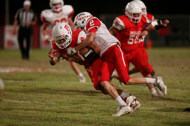 Miles' Jared Flores (8) is tackled by Christoval's Beau Jolly (2) on Friday, Nov. 2, 2018, during their game in Miles.