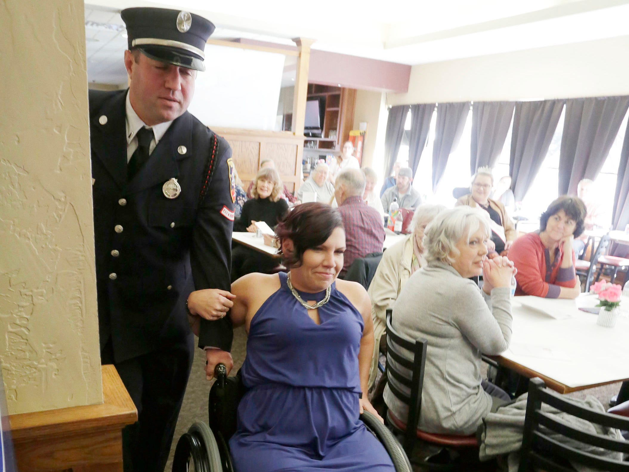 Contestant Autumn Neugent, of Madison, Wis., is escorted by a Sheboygan firefighter before speaking at the Ms. Wheelchair, Wisconsin, Saturday, November 3, 2018, in Plymouth, Wis. Neugent took top honors. Neugent suffers from Multiple Sclerosis.