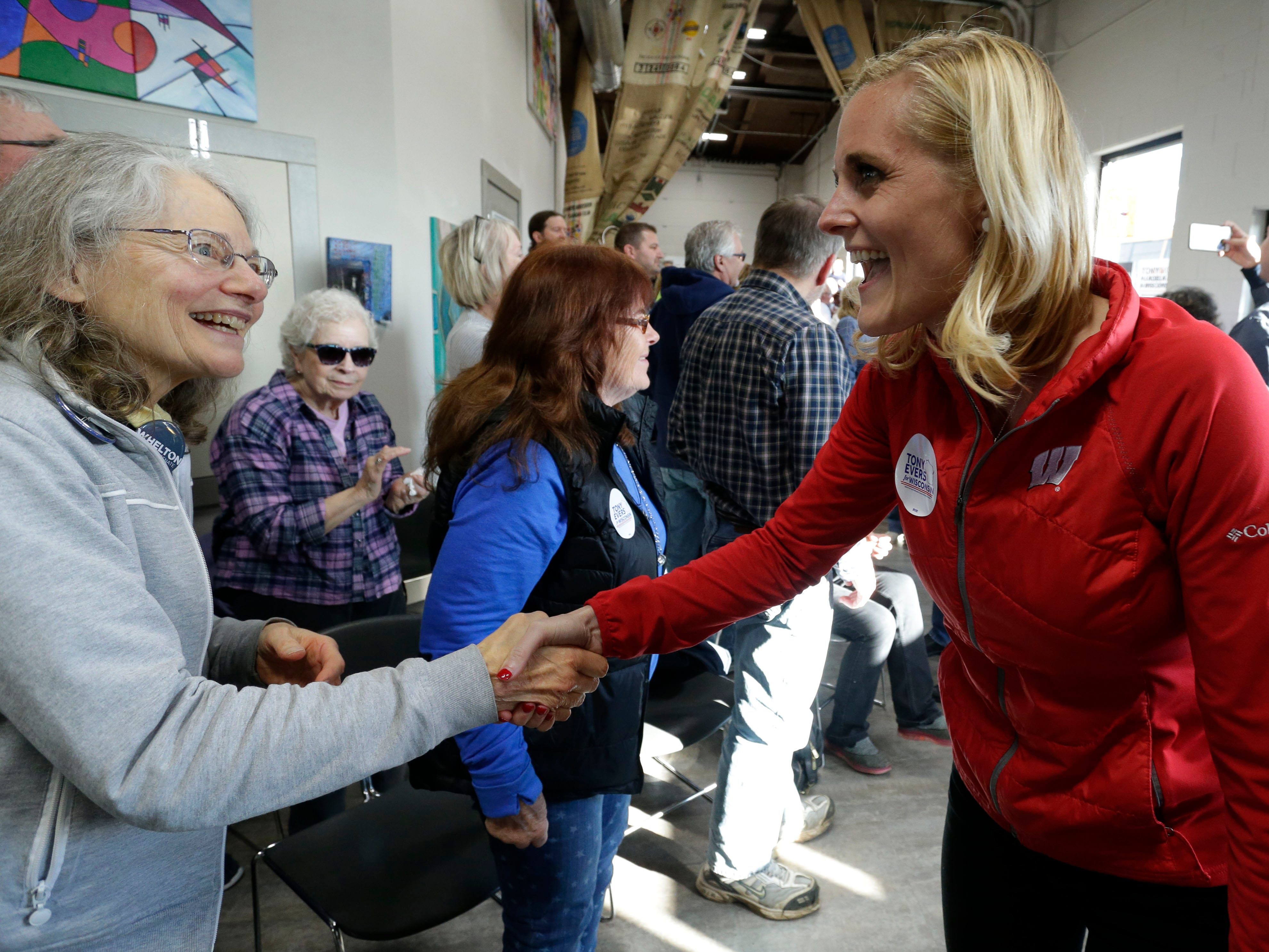 Wisconsin Treasury Candidate Sarah Godlewski shakes hand at The Hub coffee shop during a campaign visit, Saturday, November 3, 2018, in Plymouth, Wis.