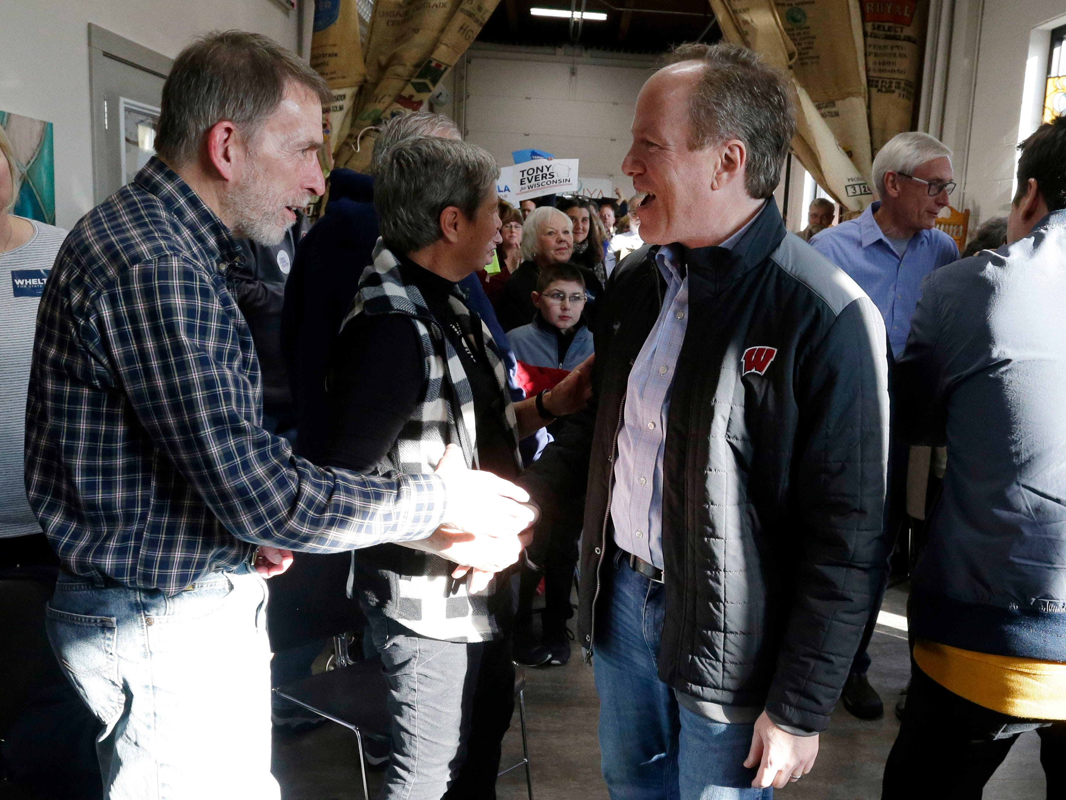 U.S. representative candidate Dan Kohl, right, shakes hands during a campaign stop at The Hub coffee shop, Saturday, November 3, 2018, in Plymouth, Wis.