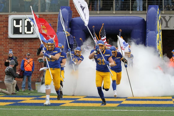 South Dakota State players carry flags out of the tunnel for Military Appreciation Day before the match up with Missouri State Saturday afternoon at Dana J. Dykhouse Stadium in Brookings.