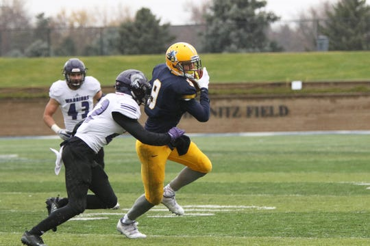 Nickel Meyers of Augustana turns to run the ball after a reception as Cole Monckton of Winona State gets set to make the tackle during Saturday's game in Sioux Falls.