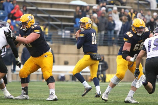 Augustana QB, Kyle Saddler drops back to pass as Brett Kramer (78) and Tom Green (68) block during Saturday's game against Winona State in Sioux Falls.