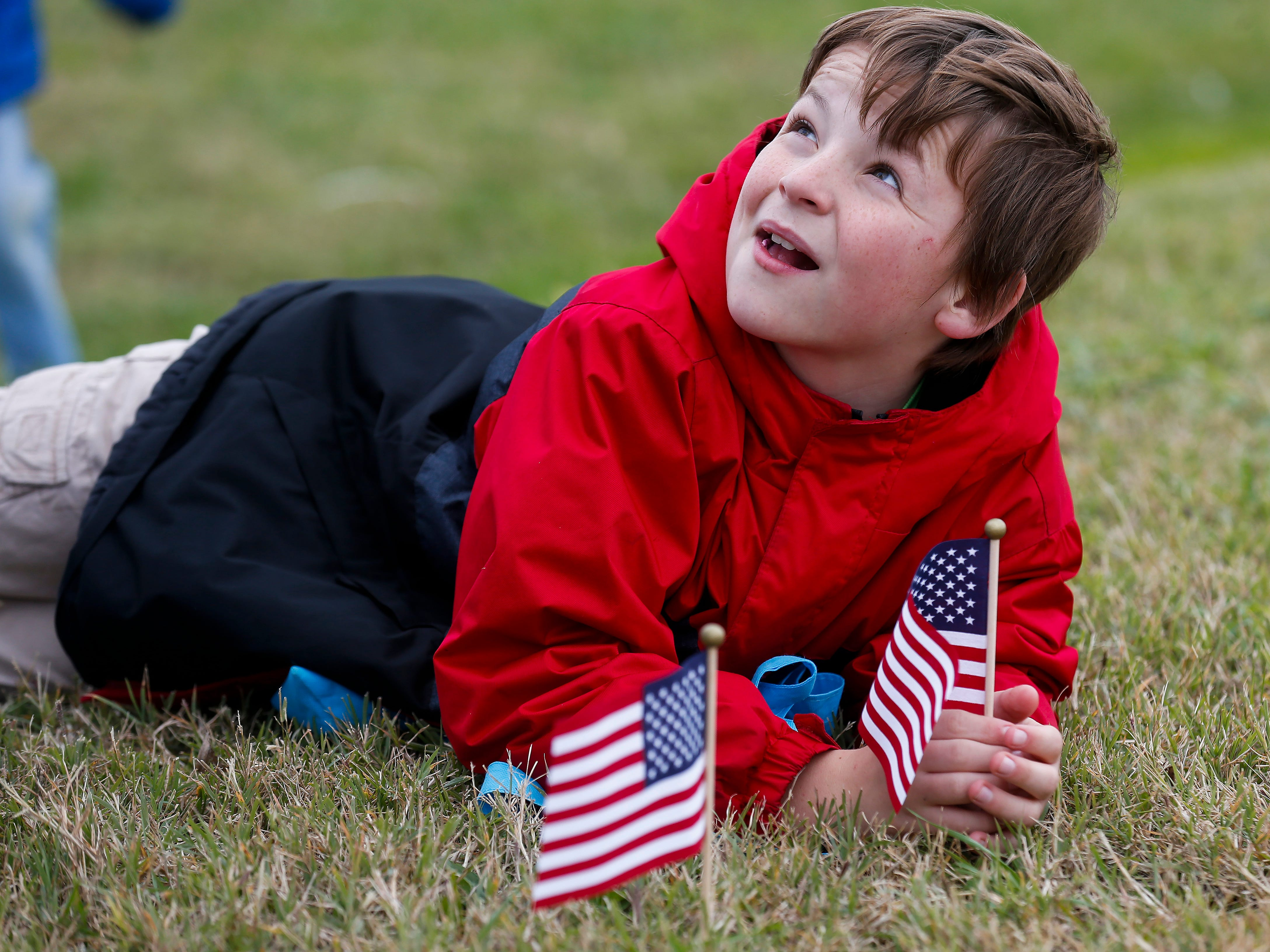 Avory Sutton, 11, puts flags in the ground along East Jackson Street in Willard for the 2nd Annual Western Greene County Veterans Day Parade on Saturday, Nov. 3, 2018.