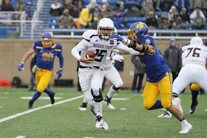 Missouri State's Peyton Huslig (15) tries to escape a sack by South Dakota State's Christan Rozeboom during the first quarter of the Bears' match up with the Jackrabbits Saturday afternoon at Dana J. Dykhouse Stadium in Brookings, SD.