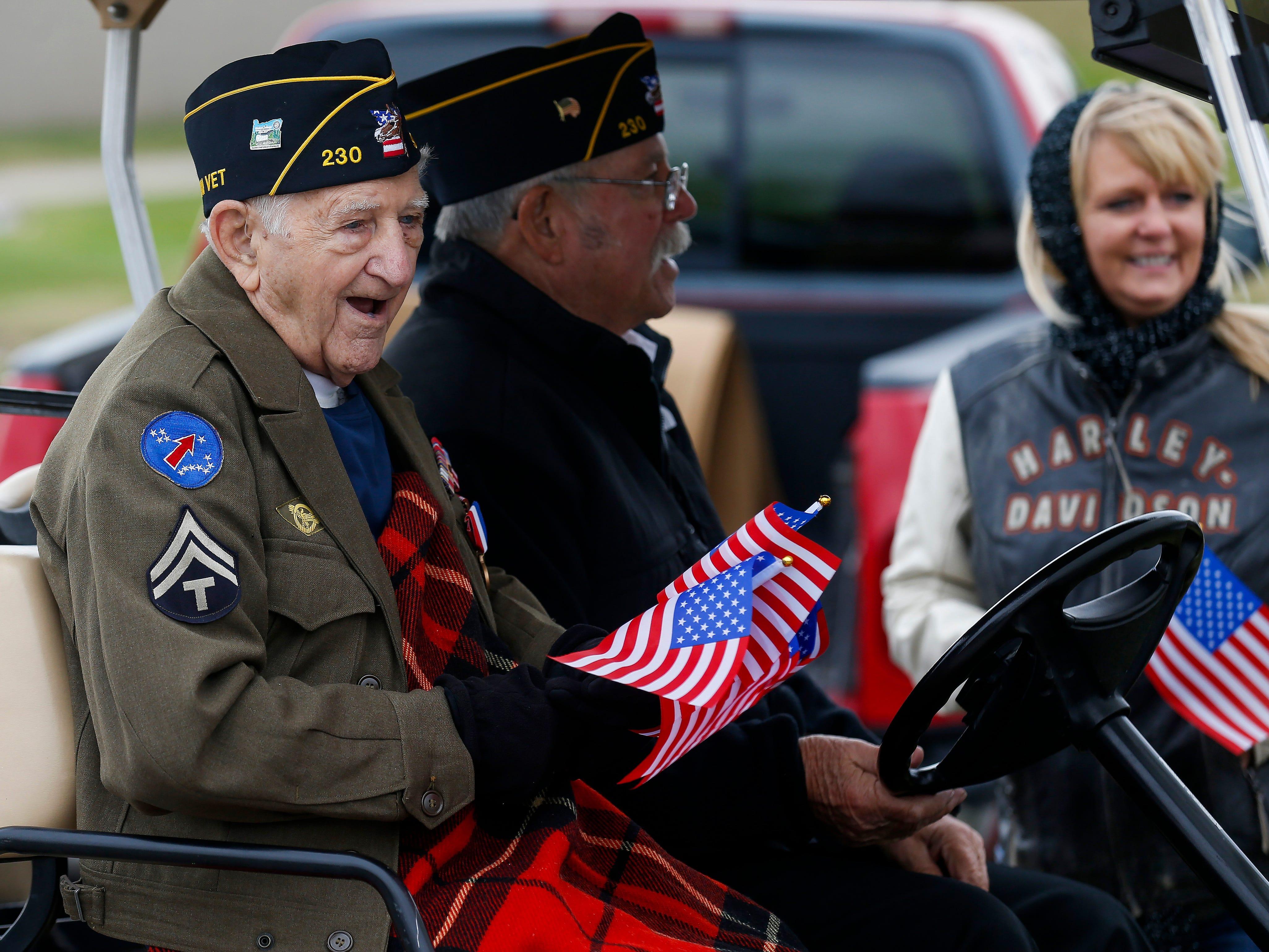 World War II veteran Leonard Branecki hands out flags in Willard for the 2nd Annual Western Greene County Veterans Day Parade on Saturday, Nov. 3, 2018.