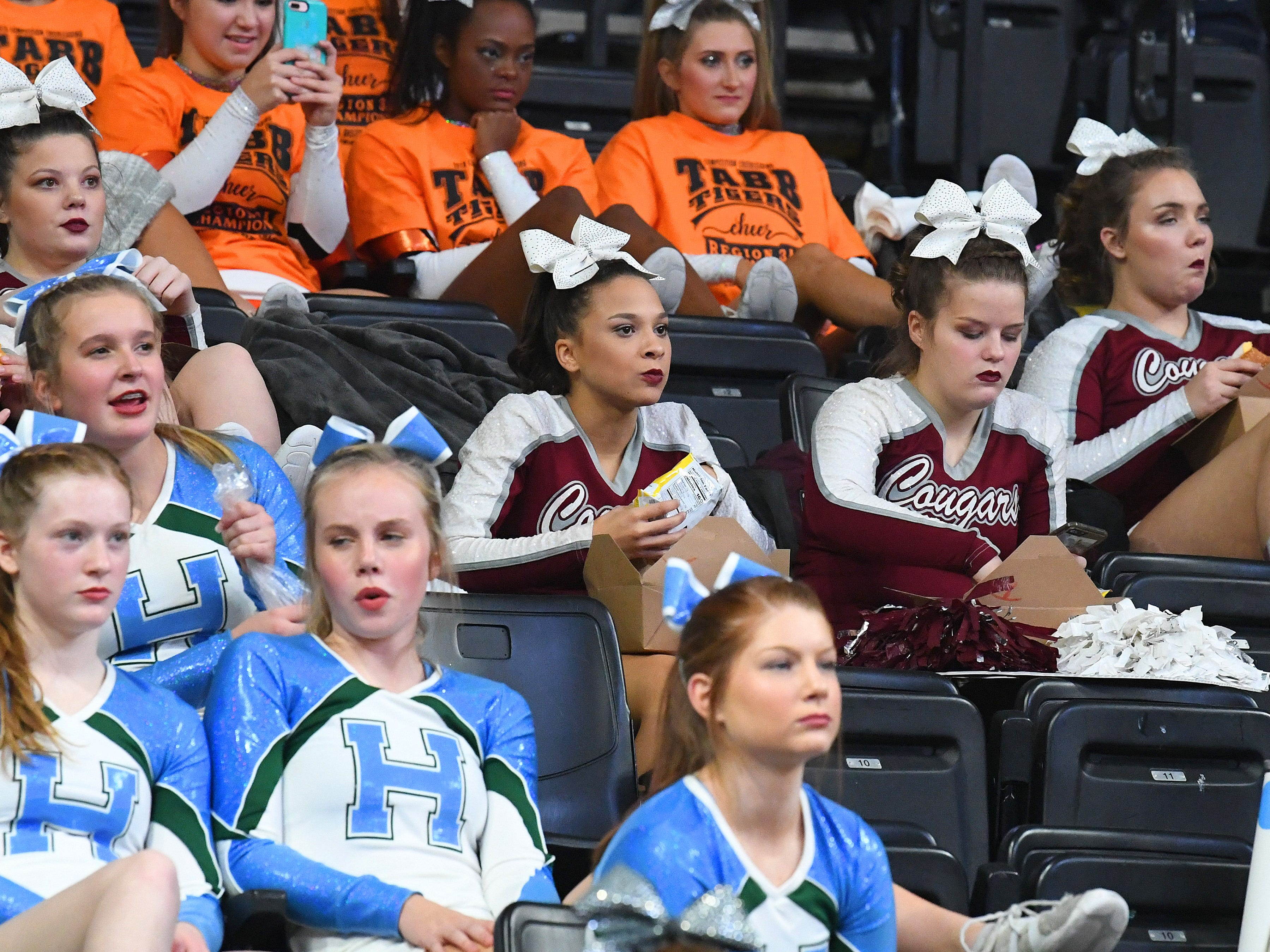 Stuarts Draft's competition cheer team sit together surrounded by other teams as they wait to hear if they will advance out of the first round and into the finals during the VHSL Competition Cheer Championships in Richmond on Saturday, Nov. 3, 2018.