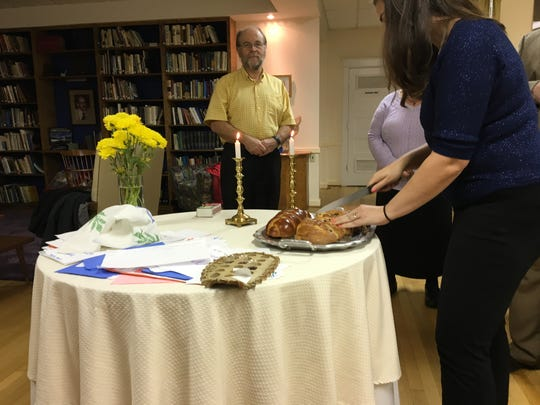 Aleeza Wilkins cuts the challah loaf, signaling the start of the Shabbat dinner Friday evening.