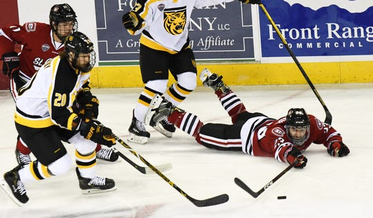 St. Cloud State's Robby Jackson (23) reaches for the puck as Colorado College's Alex Pernitsky (20) skates toward it Friday at World Arena in Colorado Springs, Colo.