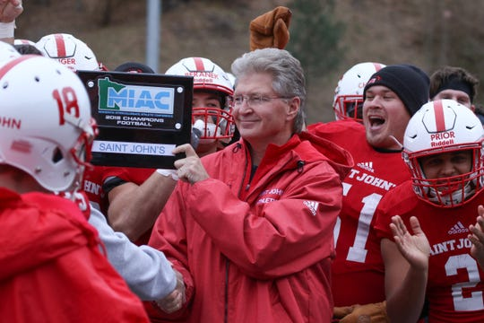 St. John's University president, Michael Hemesath, presents the football team with the MIAC championship trophy after the Johnnies beat Hamline 51-0 Saturday in Collegeville.