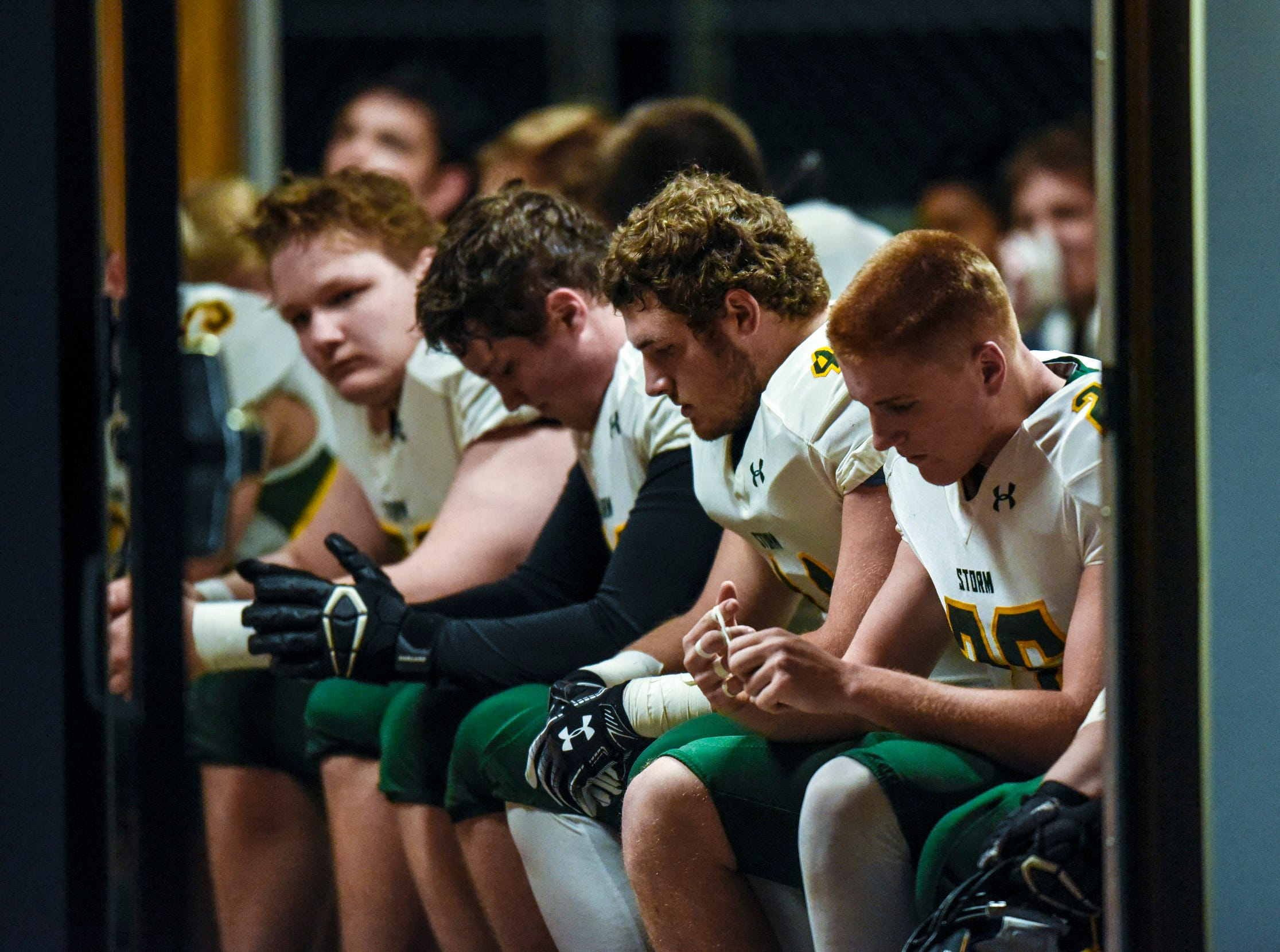 Sauk Rapids players sit quietly in a building next to the field before the start of their game against Elk River Friday, Nov. 2, in  the Section 6-5A championship at Buffalo High School.