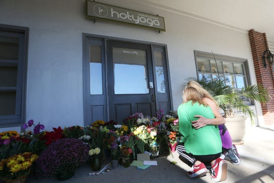 Avery Heller, daughter, left, and Victoria Heller, pay their respects to the victims of the shooting at Hot Yoga Tallahassee, the day after the tragedy, Nov. 3, 2018.