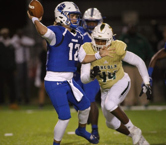Godby quarterback Trey Fisher throws a pass before Lincoln's Lee Hampton can reach him as Godby defeated Lincoln 34-24 at Gene Cox Stadium on Friday, Nov. 2, 2018.