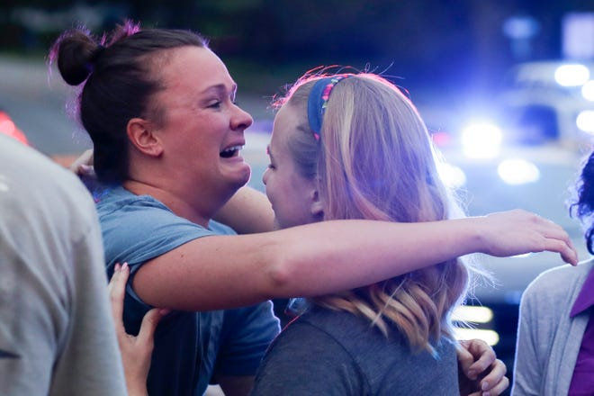 Brittani Whittington, owner of Tallahassee Hot Yoga, hugs a friend as she arrives on the scene as the Tallahassee Police Department investigates the shooting that took place at the yoga studio Friday, Nov. 2, 2018. Two women were killed during the shooting, Maura Binkley and Nancy Van Vessem.