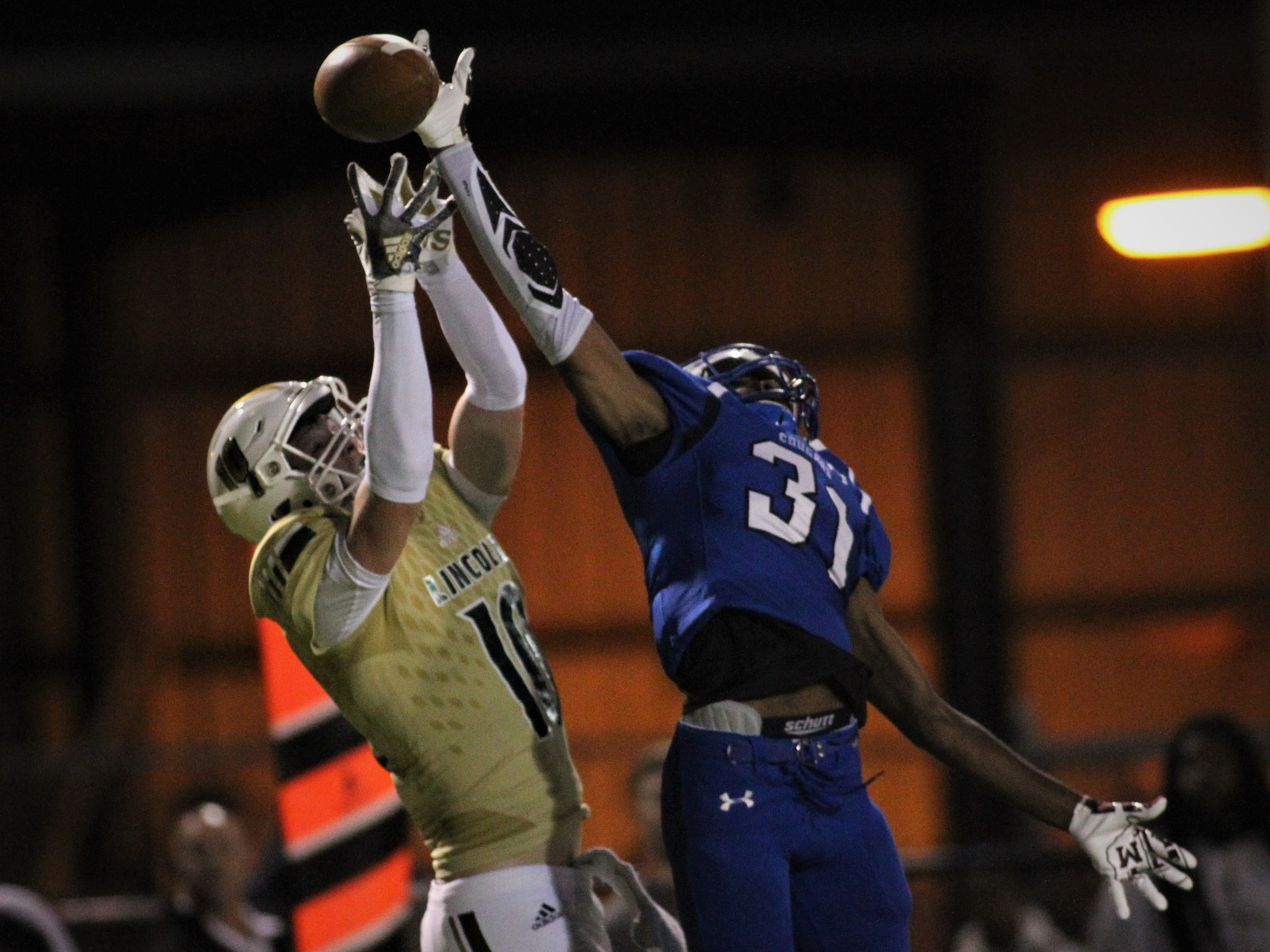 Godby defensive back Travis Cooper makes a pass break-up on a jump ball attempt to Lincoln receiver Sage Ennis as Godby defeated Lincoln 34-24 at Gene Cox Stadium on Friday, Nov. 2, 2018.