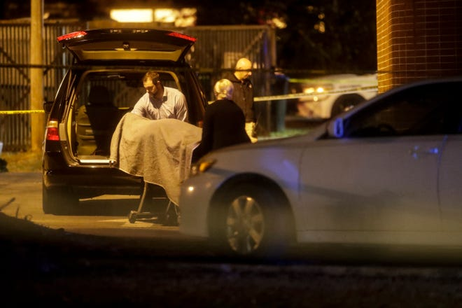 A body is removed from Hot Yoga in Betton Place near the corner of East Bradford and Thomasville roads in Tallahassee, Fla. around 12:30 a.m. Saturday, Nov. 3, 2018, following a shooting that took place there on Friday evening around 5:30 p.m.