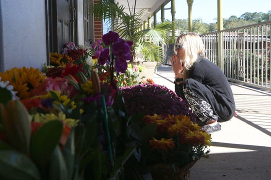Taylor Ann Johnson, who frequents Hot Yoga Tallahassee, pays her respects to the victims the day after the shooting, Nov. 3, 2018.