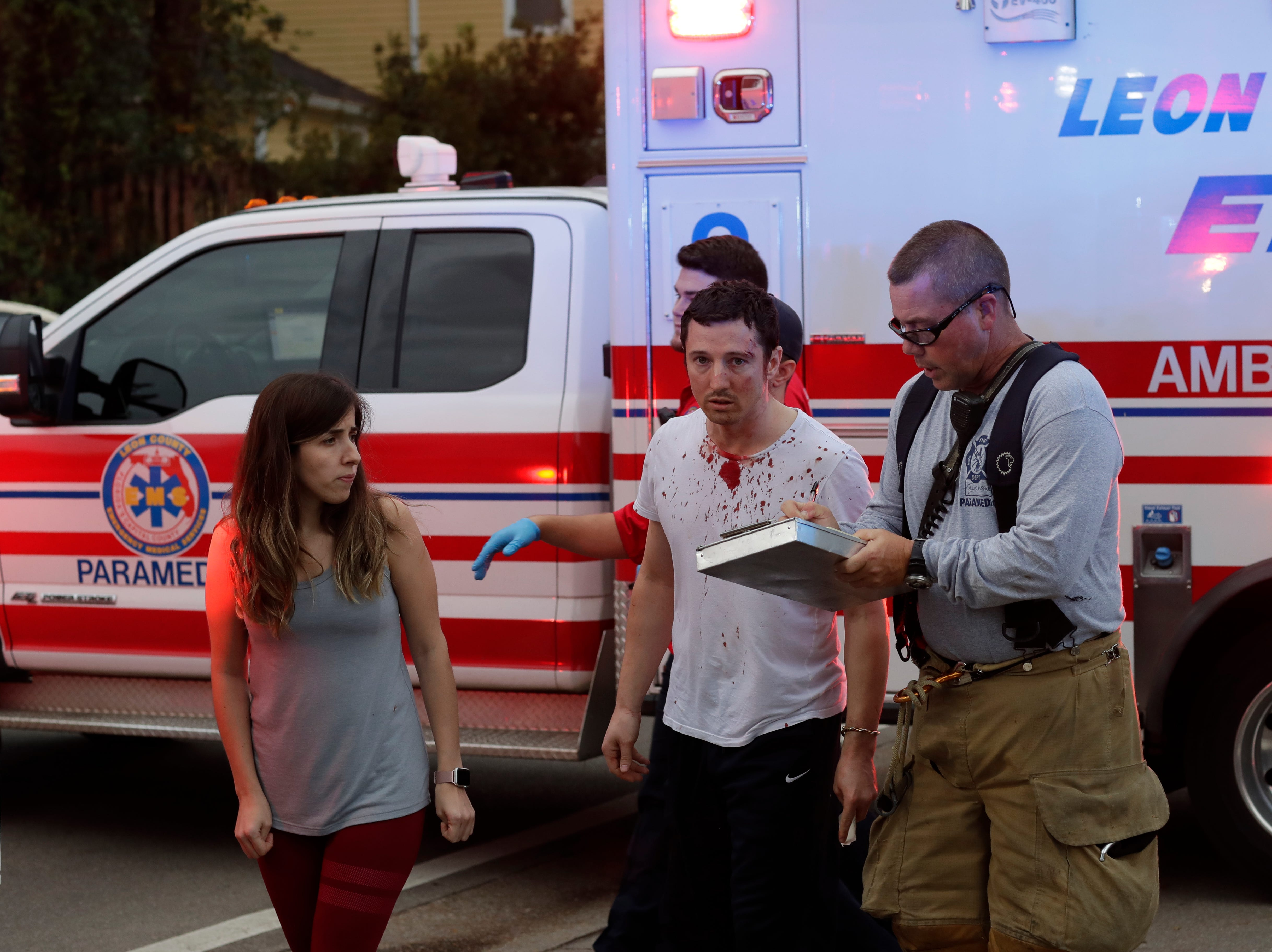 A first responder talks to Joshua Quick moments after a shooting in the Hot Yoga Studio in Midtown on Nov. 2. Quick was pistol whipped as he tried to fight off the gunman with a vacuum cleaner. He has been hailed as a hero.