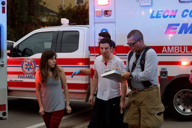 Paramedics treat Joshua Quick, center, who is being hailed as a hero for fighting off a gunman Friday, Nov. 2, 2018, at the Tallahassee yoga studio. Quick used a vacuum cleaner and broom.