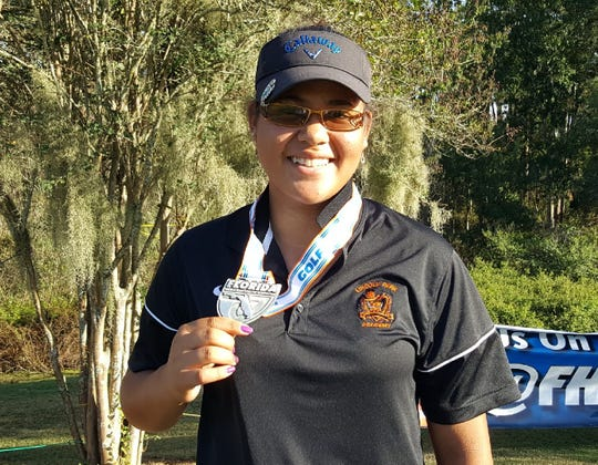 Lincoln Park Academy freshman golfer Angelica Holman shows off her medal after tying for fifth Saturday in the Class 2A girls state tournament at Howey-in-the-Hills.