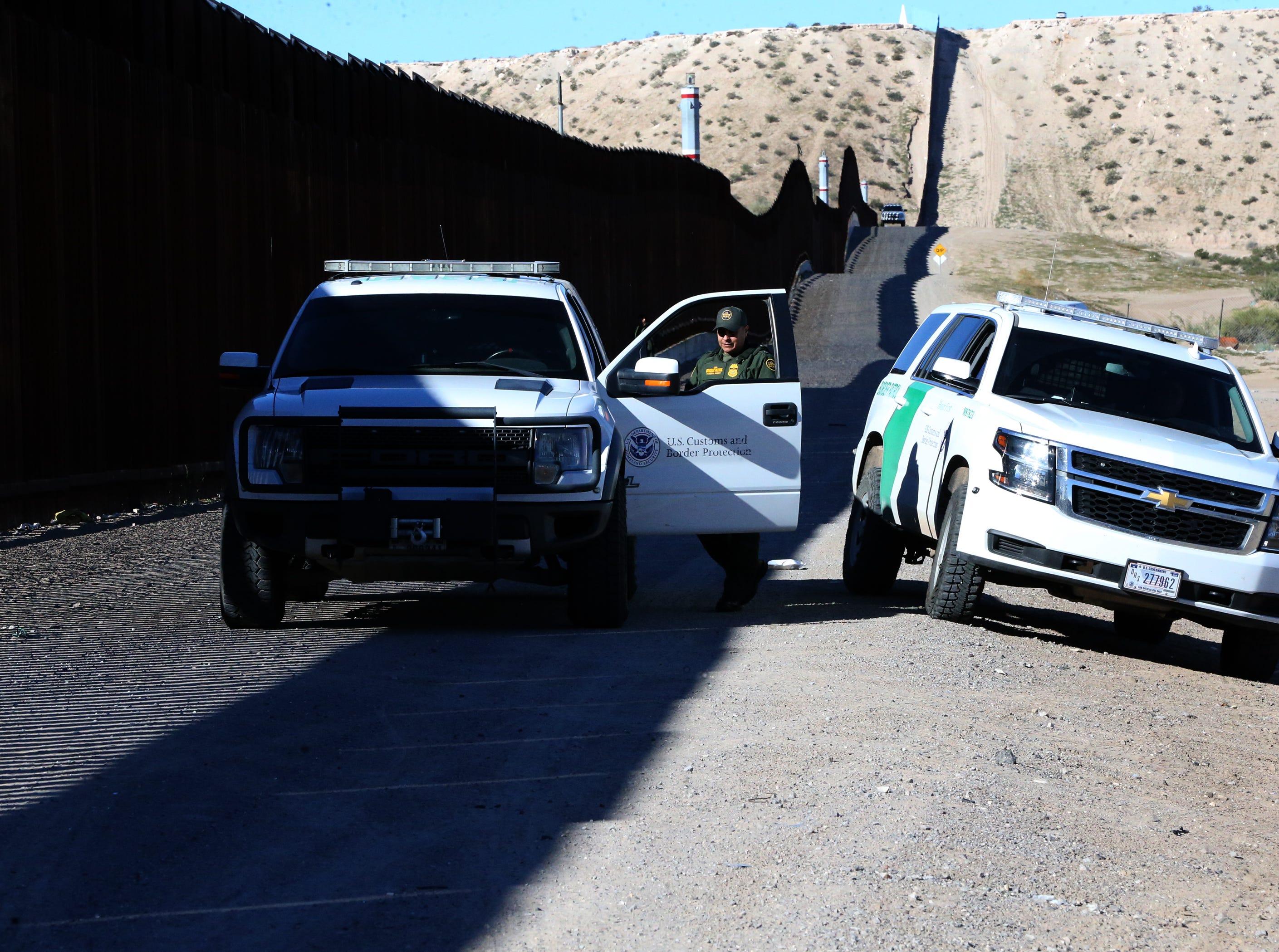 U.S. Border Patrol agents watch a gathering at the border fence Saturday.