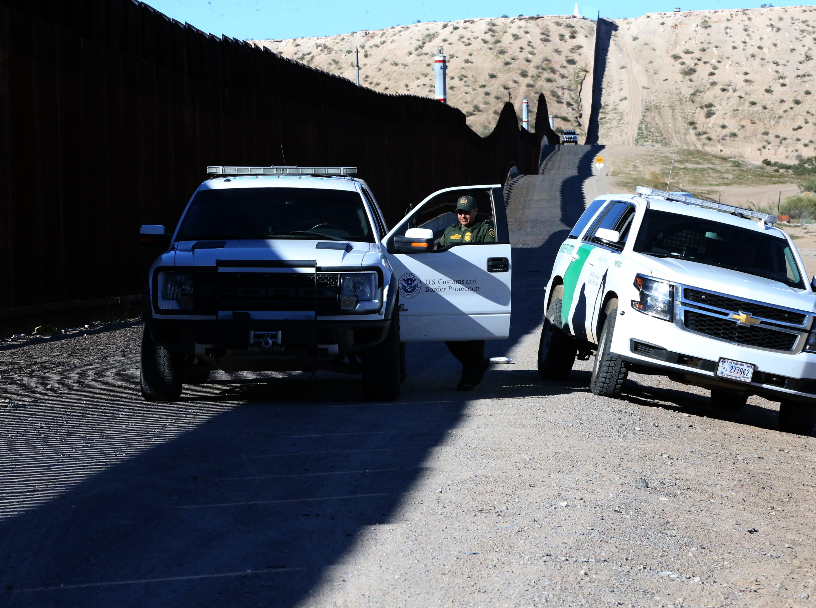 U.S. Border Patrol agents watch a gathering at the border fence Saturday.
