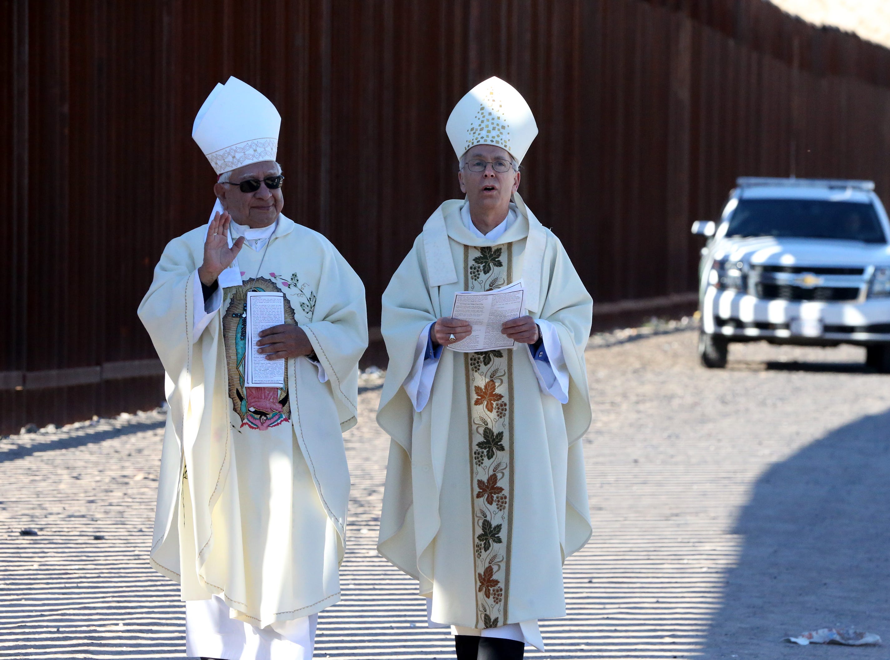 Las Cruces bishop emeritus Ricardo Ramirez, left, and El Paso bishop Mark Seitz take part in the annual Border Mass at the border fence in the Anapra area of Sunland Park, N.M. Saturday.