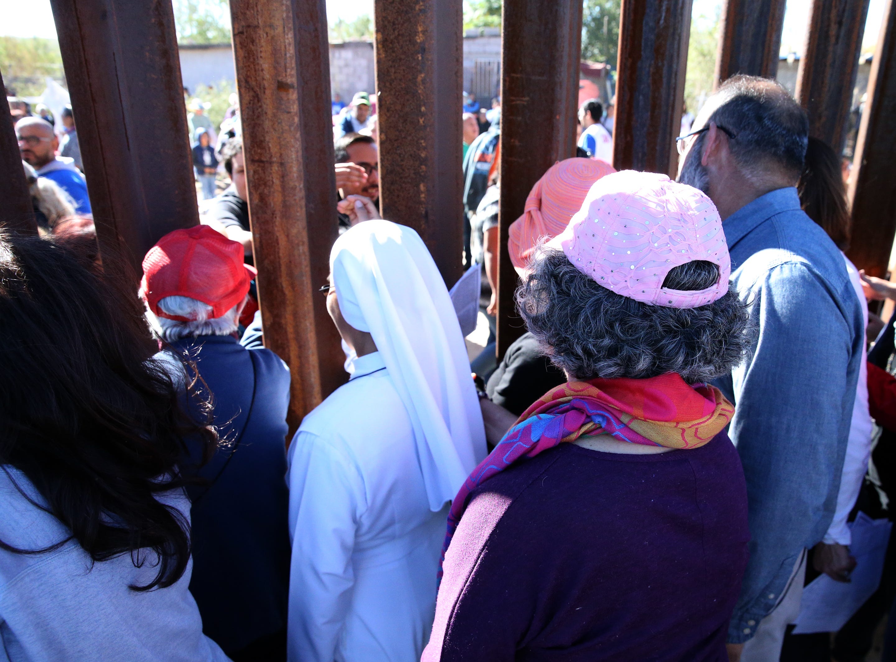 People on the U.S. side of the border fence greet those on the Mexican side at the end of a Border Mass in the Anapra area of Sunland Park, N.M. Saturday.