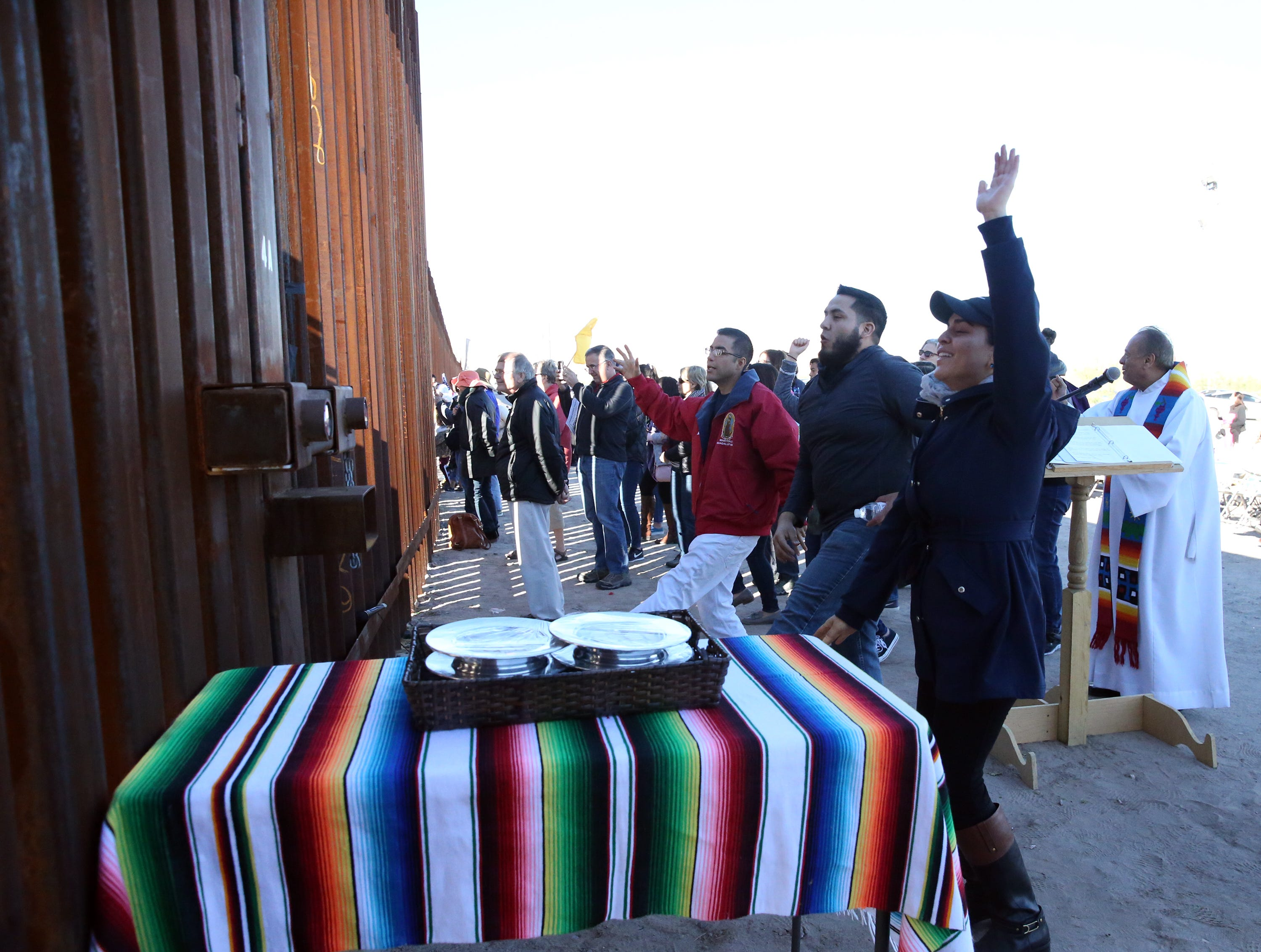 People on the U.S. side of the border fence sing and dance to music coming from the other side of the border fence Saturday.