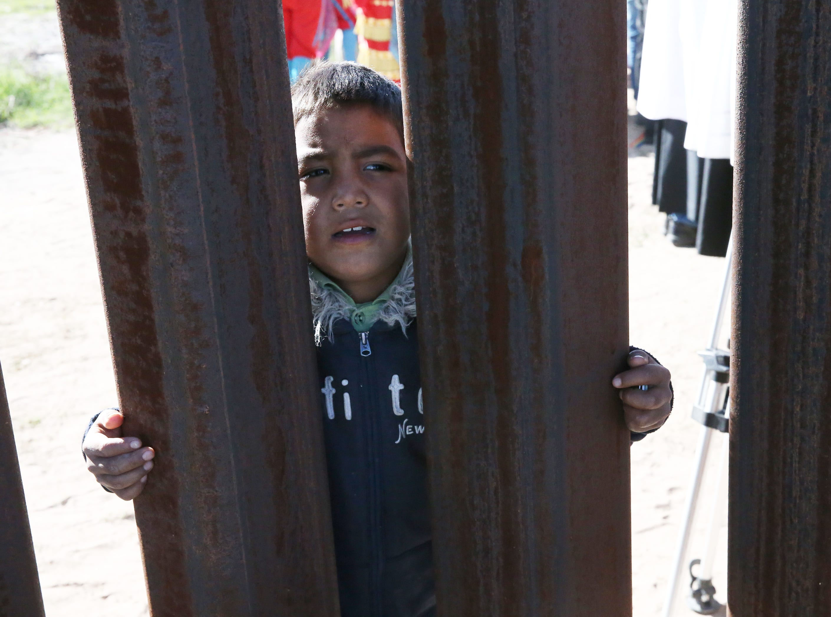 A young boy peers through the border fence from the Anapra area of Juarez Saturday.