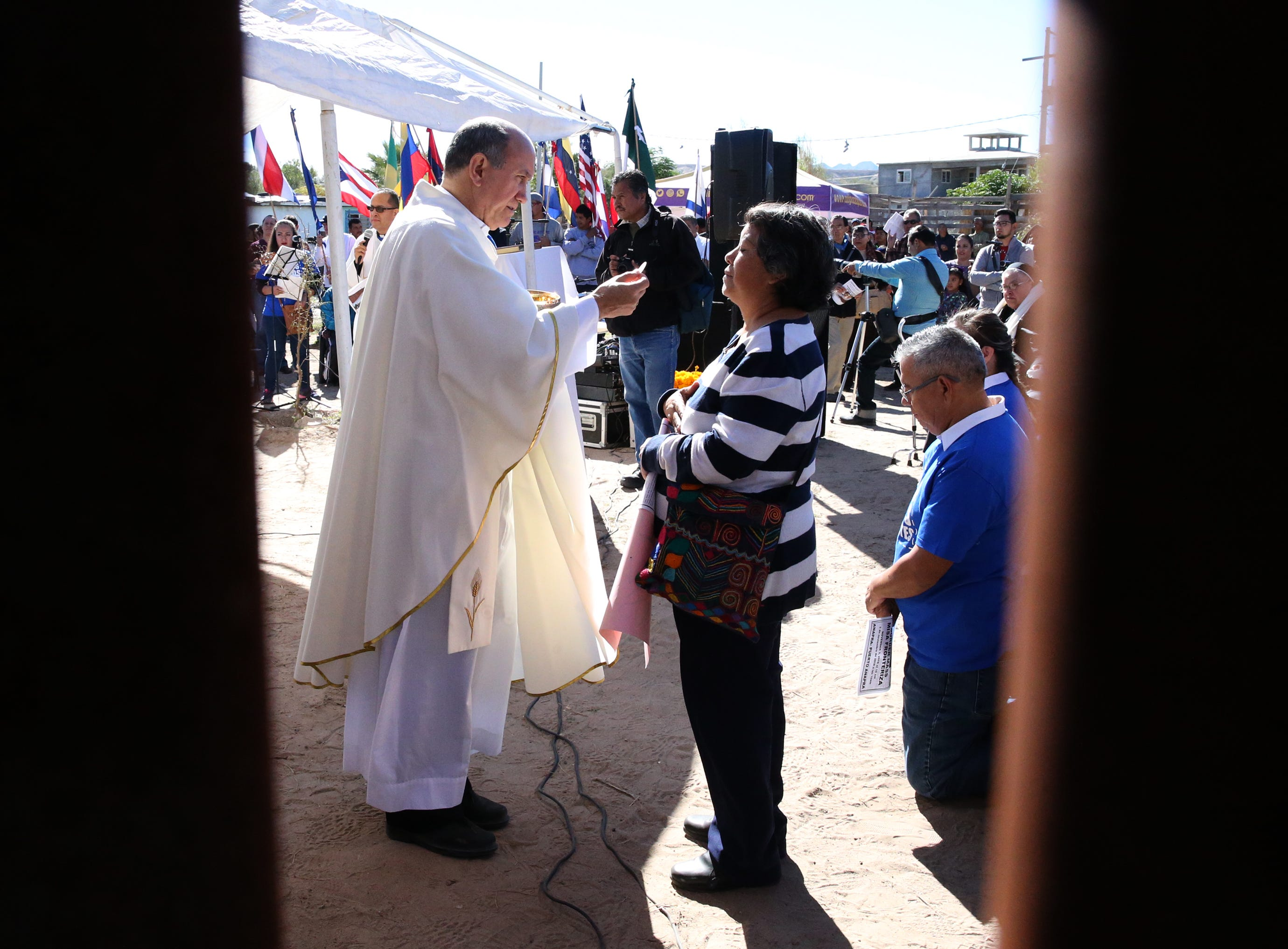 Juarez Catholic clergy administer communion to the faithful on the Juarez side of the border fence Saturday.