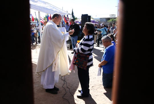 Juarez Catholic clergy administer communion to the faithful on the Juarez side of the border fence Saturday.
