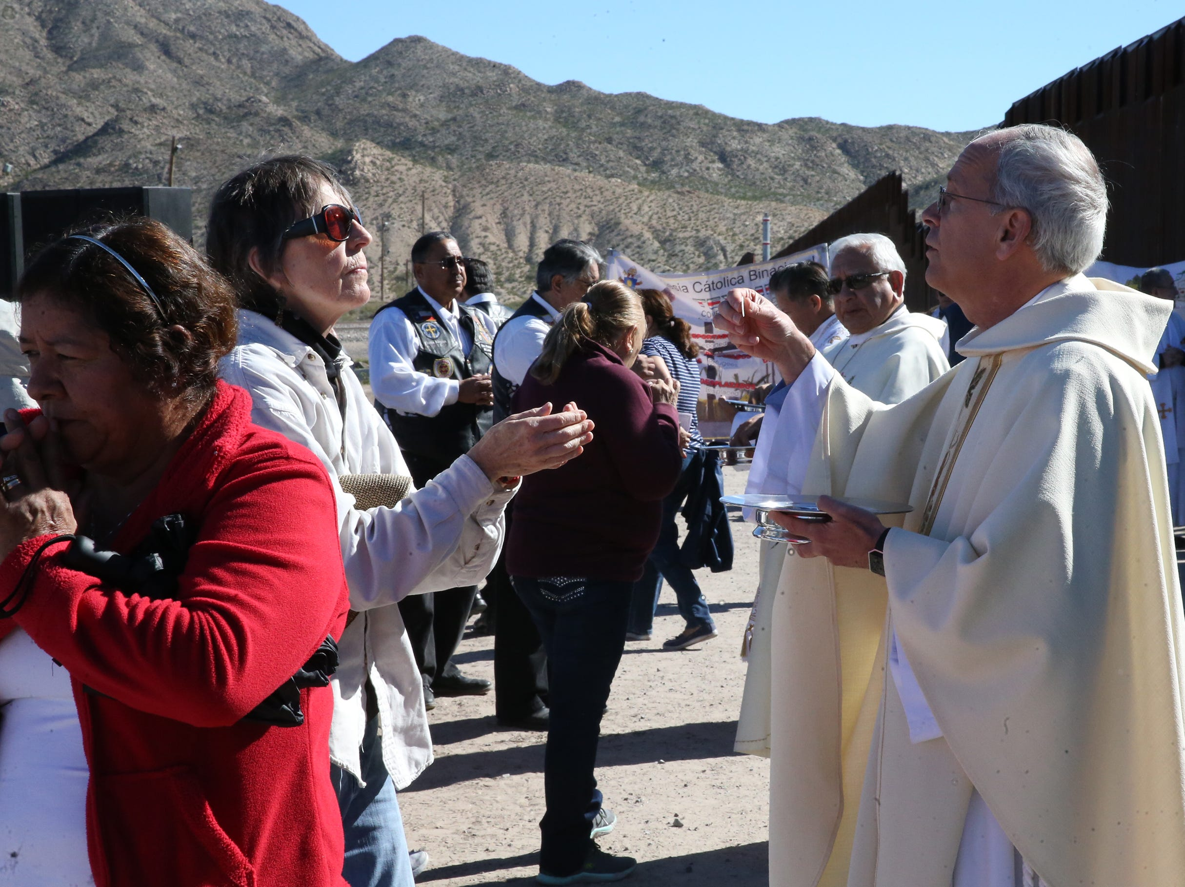 El Paso Catholic Bishop Mark Seitz, foreground, and Las Cruces bishop emeritus Ricardo Ramirez administer communion during the annual Border Mass held at the border fence in the Anapra area of Sunland Park, N.M. Saturday. The event took place on both sides of the border with Juarez Catholic clergy taking part across the fence in the Anapra area of Juarez.