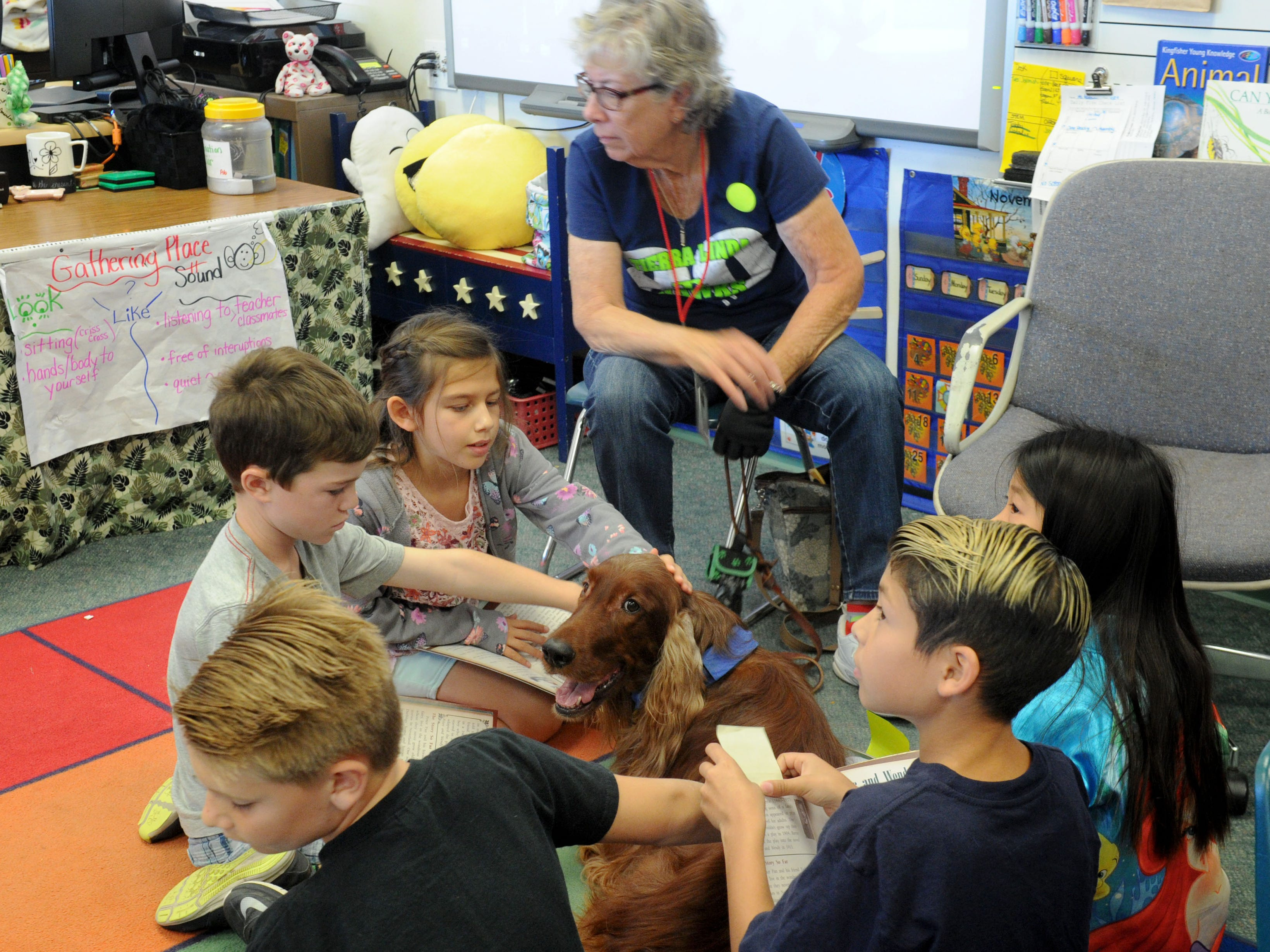 Quinn and his handler, Bobbe Jacobs, sit with a group of third-graders while they read at Tierra Linda School in Camarillo. When the dog visits the classroom, students read to him to improve their skills.